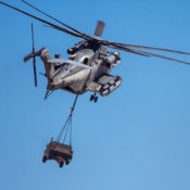 Helicopter carrying military humvee